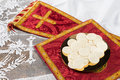 Red vestment set and communion hosts on a golden plate Royalty Free Stock Image