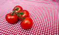 Red vine tomatoes against red and white chequered cloth Royalty Free Stock Photos