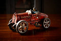Red vintage toy car  on dark wooden table Royalty Free Stock Photo
