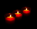 Red votive candles burning in the dark black background three symbolic traditional holders all saints day of dead etc Royalty Free Stock Photo