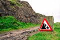 Red warning sign for falling rocks on a hill path in Edinburgh, Royalty Free Stock Photo
