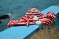 Red white bikini on beach bench with sea star and stones blue wooden with a sea in background Royalty Free Stock Photos