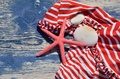 Red white bikini with red sea star and beach stones on navy blue wooden beach bench Royalty Free Stock Photography