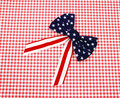 Red white and blue bow on red checkerboard Royalty Free Stock Images