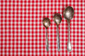 Red and white checked table cloth with old spoons silver Royalty Free Stock Images