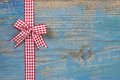 Red/white checkerd bow with a ribbon on wooden blue background f Royalty Free Stock Photo