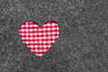 Red and white checkered heart on grey felt background for christmas bavarian concepts mother s or valentine s day Stock Image