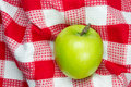 Red and white checkered table cloth with green apple Royalty Free Stock Photo
