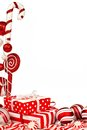 Red and white christmas border with gifts baubles and candy corner against background Stock Photo