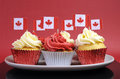 Red and white cupcakes with canadian maple leaf national flags against a background for canada day or Stock Photography
