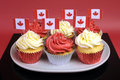 Red and white cupcakes with canadian maple leaf national flags close up against a background for canada day or Royalty Free Stock Photography