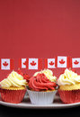 Red and white cupcakes with canadian maple leaf national flags vertical with copyspace against a background for canada day or Royalty Free Stock Photography