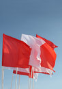 Red and white flags flutter in wind on blue sky Stock Image