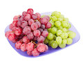 Red and white grapes bunches on plate blue isolated Stock Images