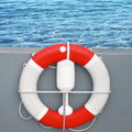 Red and white lifebuoy with rope sea water on a background Stock Photos