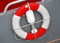 Red and white lifebuoy with rope in small boat Stock Image