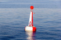 Red white moored buoy in blue sea Royalty Free Stock Images
