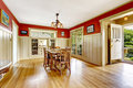 Red and white spacious dining room with exit to backayrd area in old house wall trim furnished old wooden table set has Royalty Free Stock Images