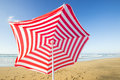 Red and white sunshade flying away travel background with a at an endless beach with a blue sky a turquoise sea playa de las pilas Royalty Free Stock Photo