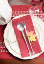 Red and white theme festive fine dining table setting vertical with autumn fall leaf decoration crystal wine glass turkey tureen Stock Photography