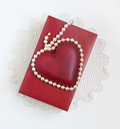 Red white valentine keepsakes cultured pearls surrounding glass heart on box sitting on top a doily Royalty Free Stock Photos