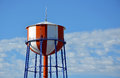 Red and white water tower striped against blue sky Stock Photography