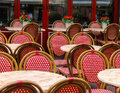 Red and white wicker chairs and small tables in outdoor cafe Royalty Free Stock Photo