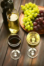Red and white wine in glasses of with globe grapes bottles of the back photographed on dark wood with Royalty Free Stock Photo