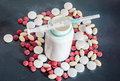 Red white yellow drugs pills with white open plastic bottle s syringe powder bunch medical homeopathic black background close up Royalty Free Stock Photos