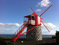 Red windmill in azores typical pico island portugal it has a dome and with flemish tradition atlantic sea can be seen on the Royalty Free Stock Image