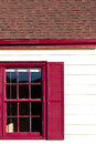 Red windon and gutters accent on the white house siding brown roof Royalty Free Stock Photo