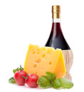 Red wine bottle cheese and tomato still life isolated on white background cutout italian food concept Royalty Free Stock Images