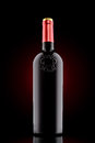 Red wine bottle with emboss at the black background with red spot