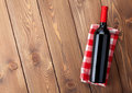 Red wine bottle over towel on wooden table