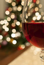 Red wine for christmas closeup shot of a glass of with glittering tree lights in the background Royalty Free Stock Photo