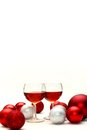 Red wine and christmas decorations isolated on white background two glasses filled with sit an surrounded by silver sparkling bulb Royalty Free Stock Images