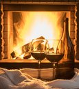 Red wine on cozy fireplace background, close up. Royalty Free Stock Photo