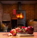 Red wine and fruit in front of burning fire bottle glass with apple strawberries on wooden table roaring inside wood stove Royalty Free Stock Photography