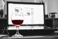 Red wine in glass with computer laptop on wooden table, relaxing while working Royalty Free Stock Photo