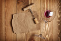 Red wine glass corkscrew and paper for your note on wooden table background Stock Image