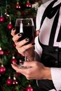 Red wine glass in girl hands in elegant dress with tie and Christmas tree in background Royalty Free Stock Photo