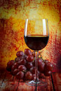 Red wine in a glass with grapes Royalty Free Stock Photos