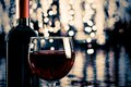 Red wine glass near bottle with light bokeh Royalty Free Stock Photo