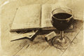 Red wine glass and old book on wooden table. vintage filtered image. black and white style photo Royalty Free Stock Photo