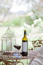 Red wine and glasses unmarked bottle with two poured on outdoor garden table Royalty Free Stock Photos