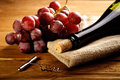 Red wine and grapes in vintage setting Stock Photos