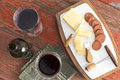 Red wine with harvati cheese and spicy sausage bottle of two full glasses served sliced as a tasty appetizer to dinner on a Royalty Free Stock Photo