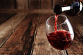 Red wine is poured from bottle to glass Royalty Free Stock Photo
