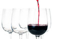 Red wine pouring into empty glass tasting closeup on a white background isolated Stock Image