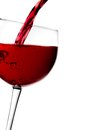 Red wine pouring into half glass tilted with space for text Royalty Free Stock Photo